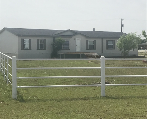 tan/blue home with white fence and green grass